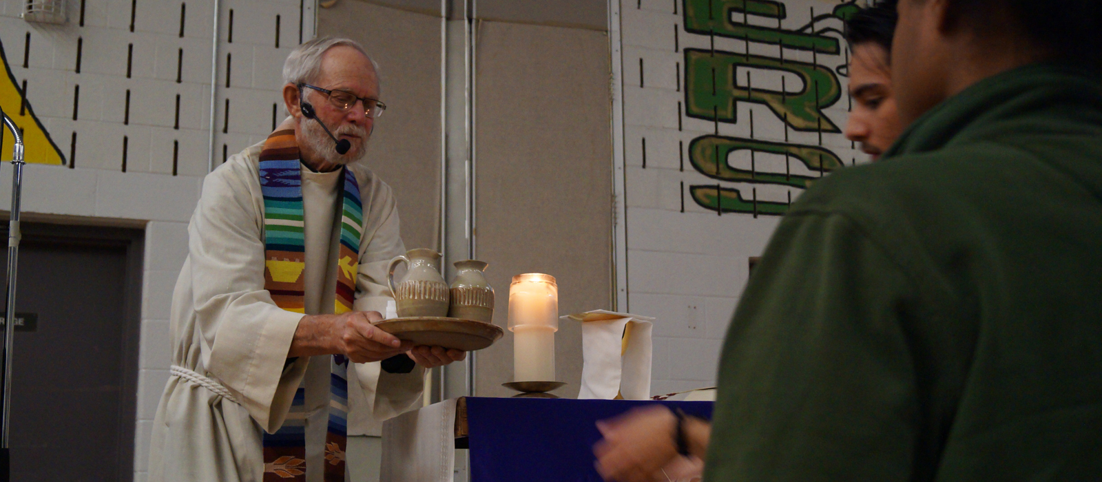Priest saying Mass in school gym