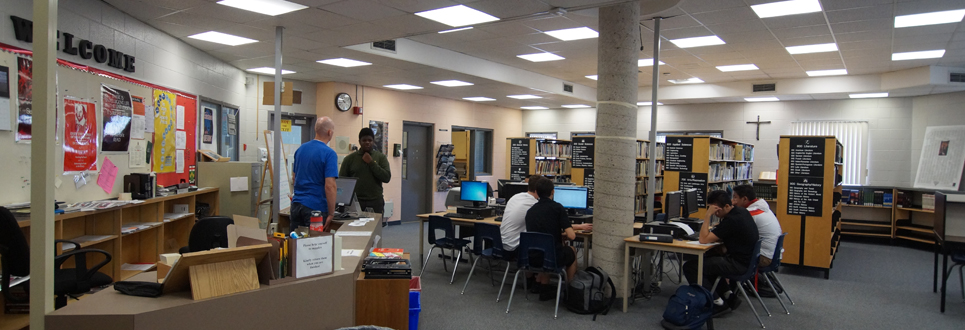Male student talking to male teacher in the Library Learning Commons