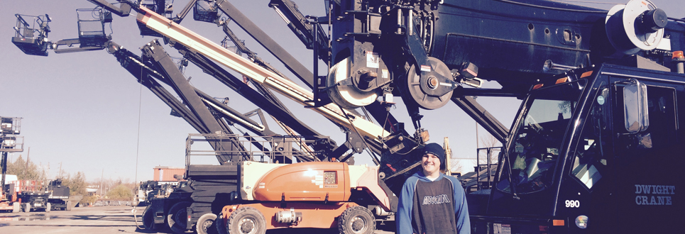 student with large machine cranes behind him